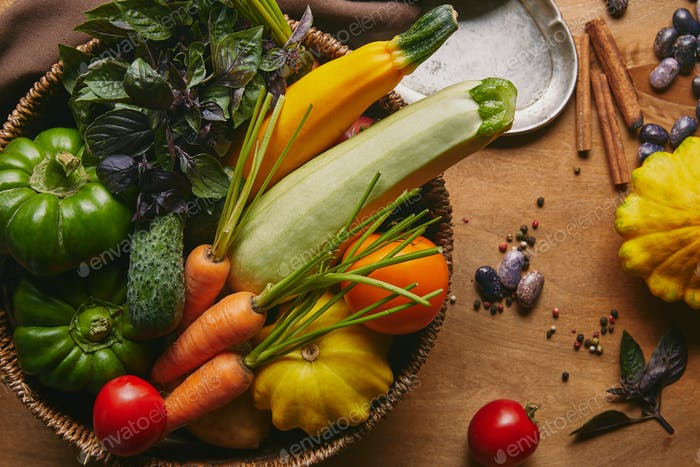 Basket filled with farm vegetables on wooden table