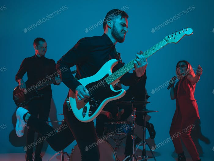 Young caucasian musicians, band performing in neon light on blue studio background, guitarist in