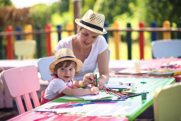 mom and little daughter drawing a colorful pictures