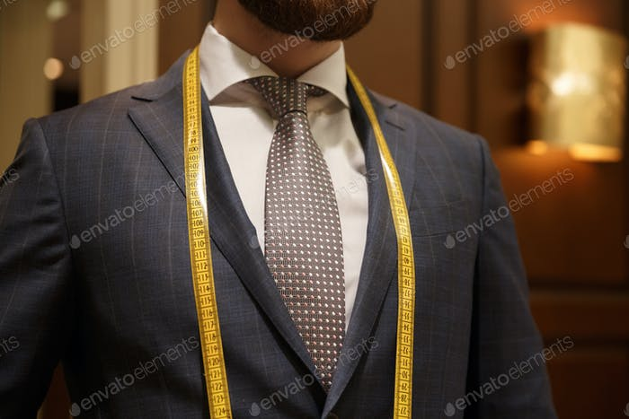 Cropped image of bearded man with measuring tape on neck