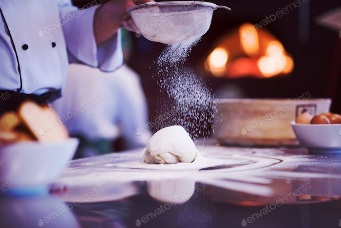 chef sprinkling flour over fresh pizza dough