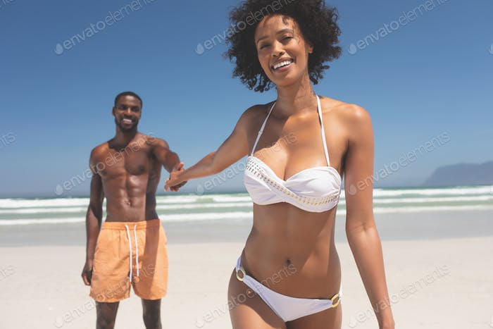 Man holding hand of beautiful woman at beach on sunny day