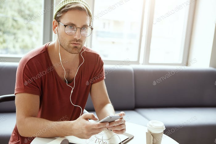 Attractive young bearded male songwriter sitting at cafe table in earphones, listening to audiotrack