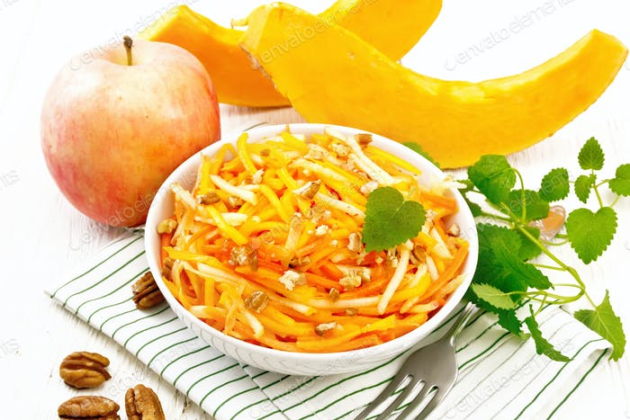 Salad of pumpkin and apple in bowl on board