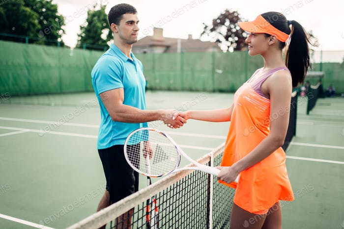 Man and woman partners on outdoor tennis court