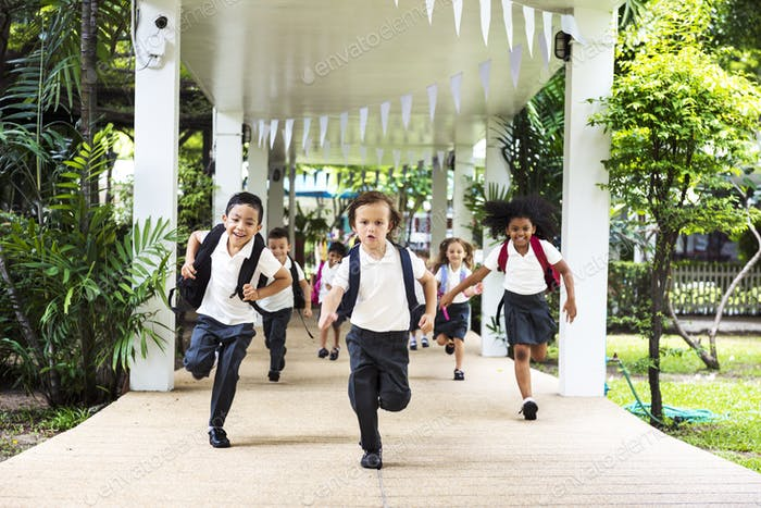 Group of diverse kindergarten students running cheerful after sc