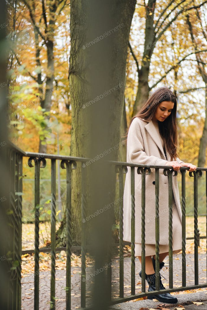 Attractive casual brunette girl in coat thoughtfully walking alone in park