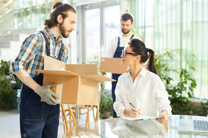 Female entrepreneur talking to movers in new restaurant