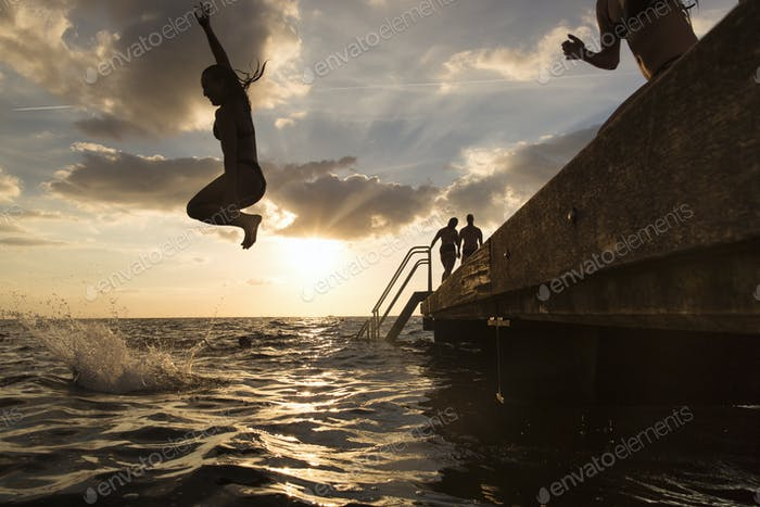 Young woman diving into sea at sunset