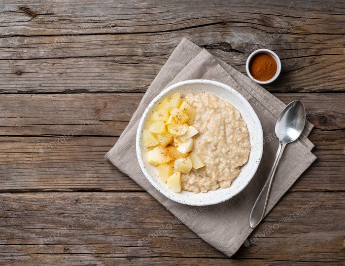 Large bowl of tasty and healthy oatmeal with apple for Breakfast, morning meal.
