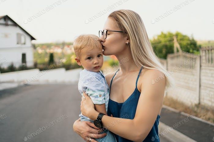 Junge Frau küsst die Stirn ihres Sohnes