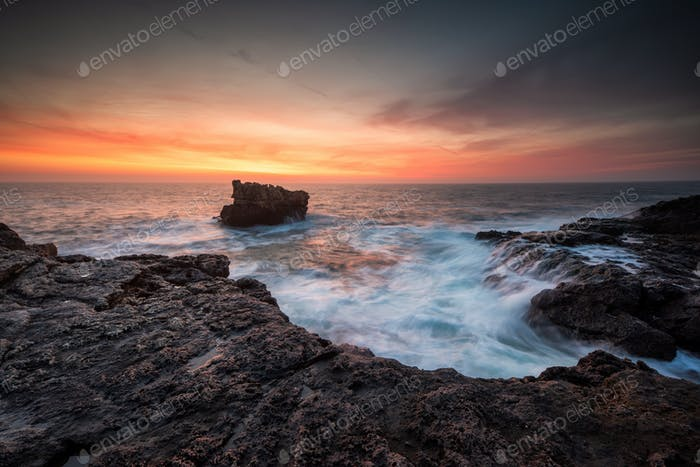Sea sunrise at rocky beach