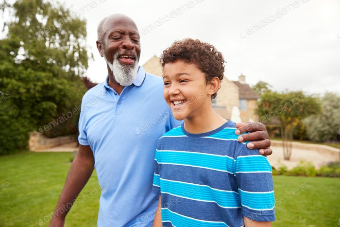 Grandfather With Grandson Walking In Garden At Home