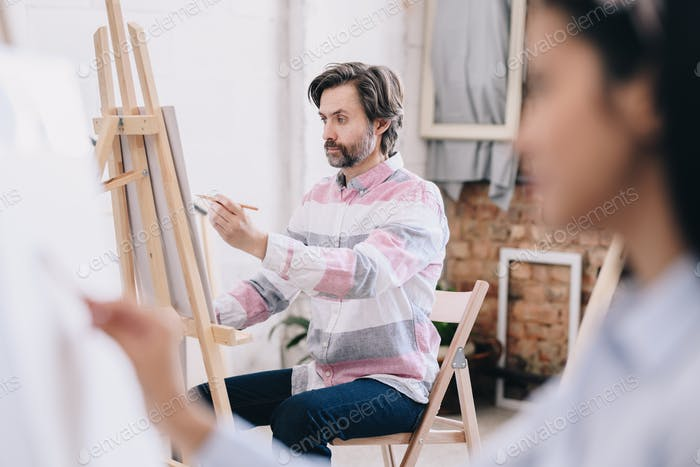 Mature Artist Painting in Studio