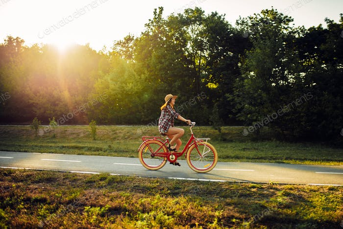 Woman riding on vintage bicycle in summer park