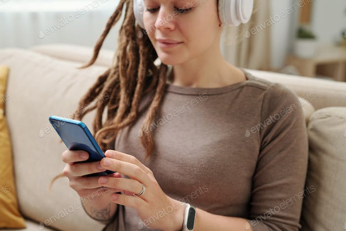 Hands of young woman with headphones scrolling in smartphone for music