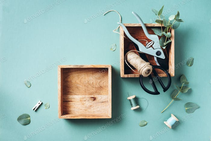 Eucalyptus branches and leaves, garden pruner, scissors, wooden boxes over green background with