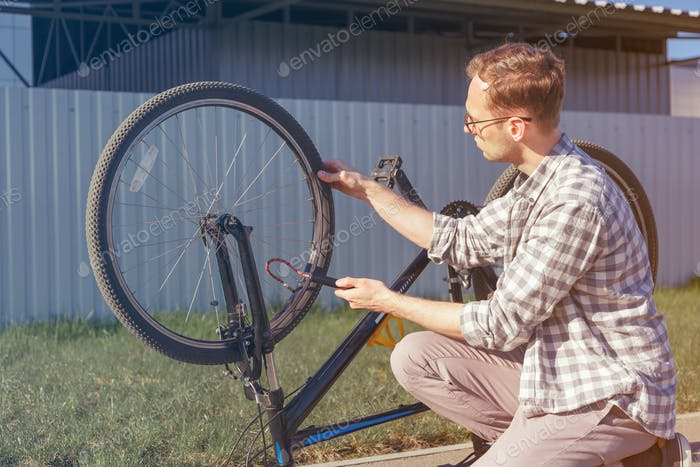 Man uses a bicycle pump. Cyclist repairs bike in trip.