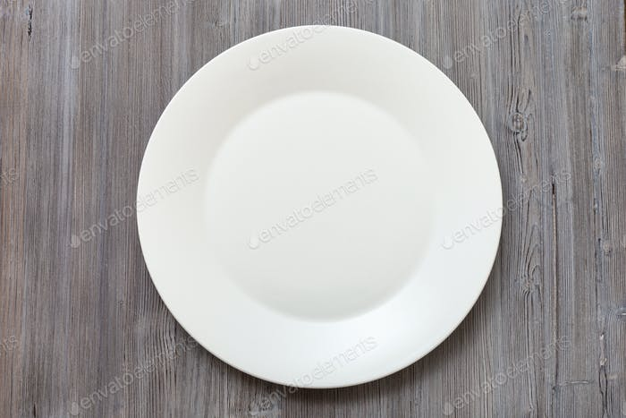 above view of white plate on gray brown table