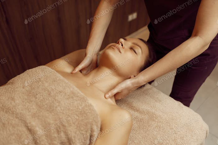 Female masseur pampering neck to young slim woman