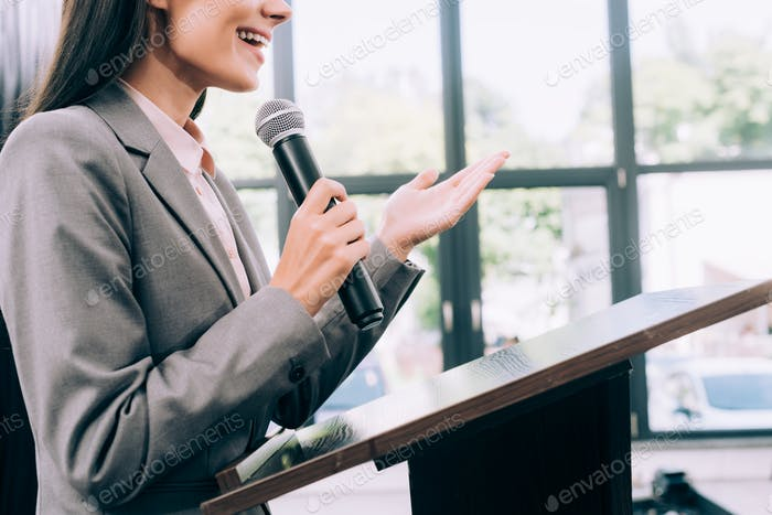 cropped image of smiling lecturer talking into microphone and gesturing at podium tribune during
