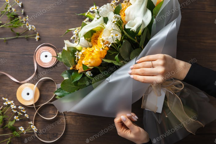 Florist at work: woman making fashion modern bouquet of different flowers on wooden background