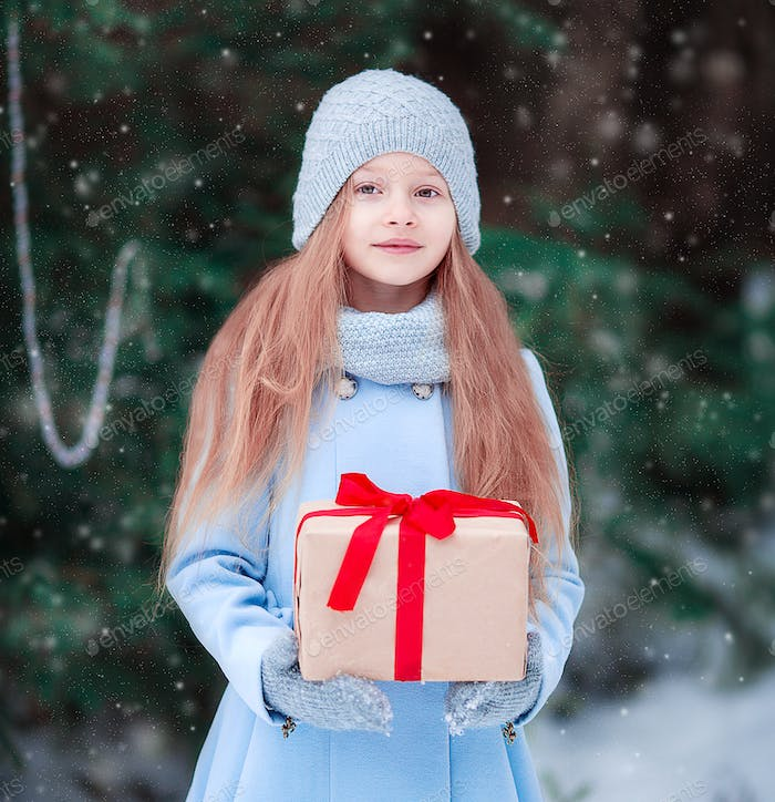Adorable little girl with christmas box gift in winter outdoors on Xmas eve