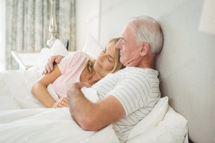 Senior couple embracing on bed