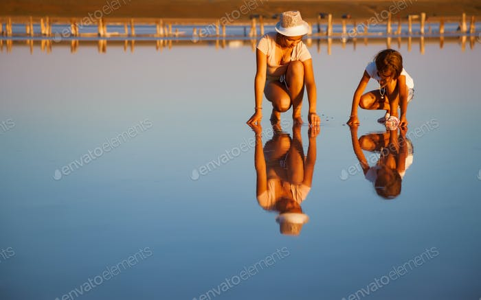Two fantastically beautiful girls on a beautiful transparent lake are looking for something in a
