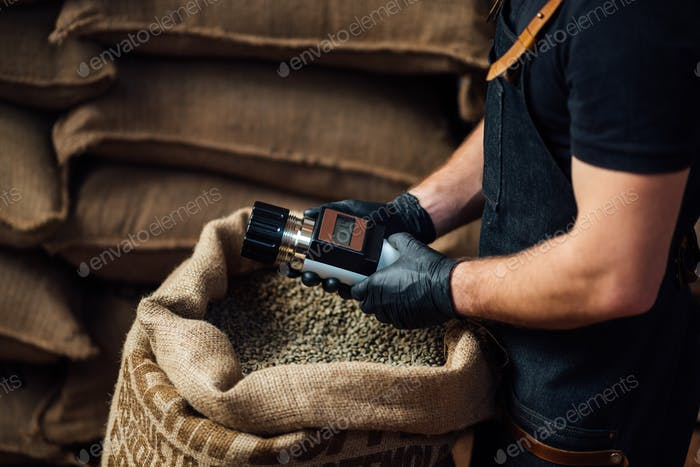 man measuring coffee beans humidity with a special electronic tester in warehouse
