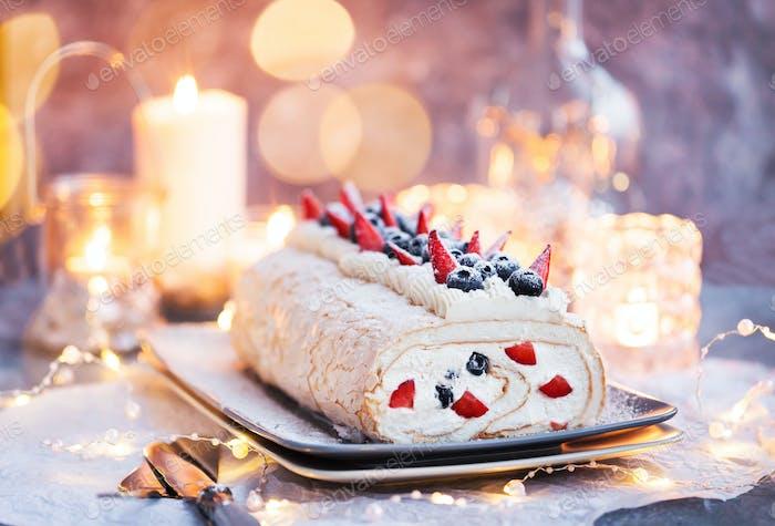 Meringue roll cake with cream and fresh berries