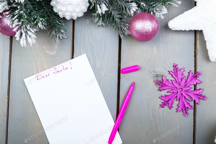 The sheet of paper, pink pencils and Christmas decorations