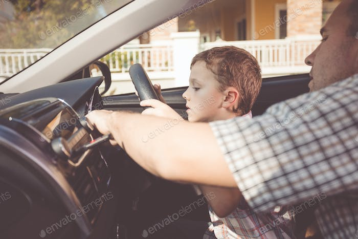 Happy father and son sitting in the car at the day time.