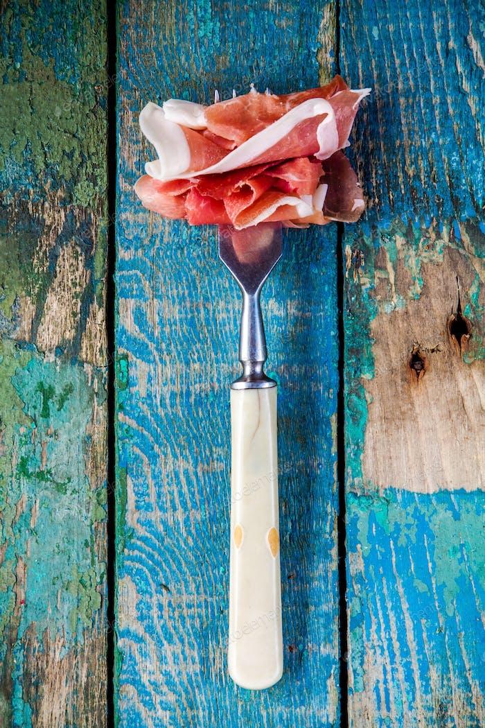 aperitivo: tenedor con prosciutto primer plano