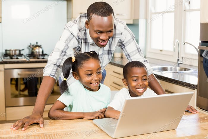 Happy family using laptop in the kitchen at home