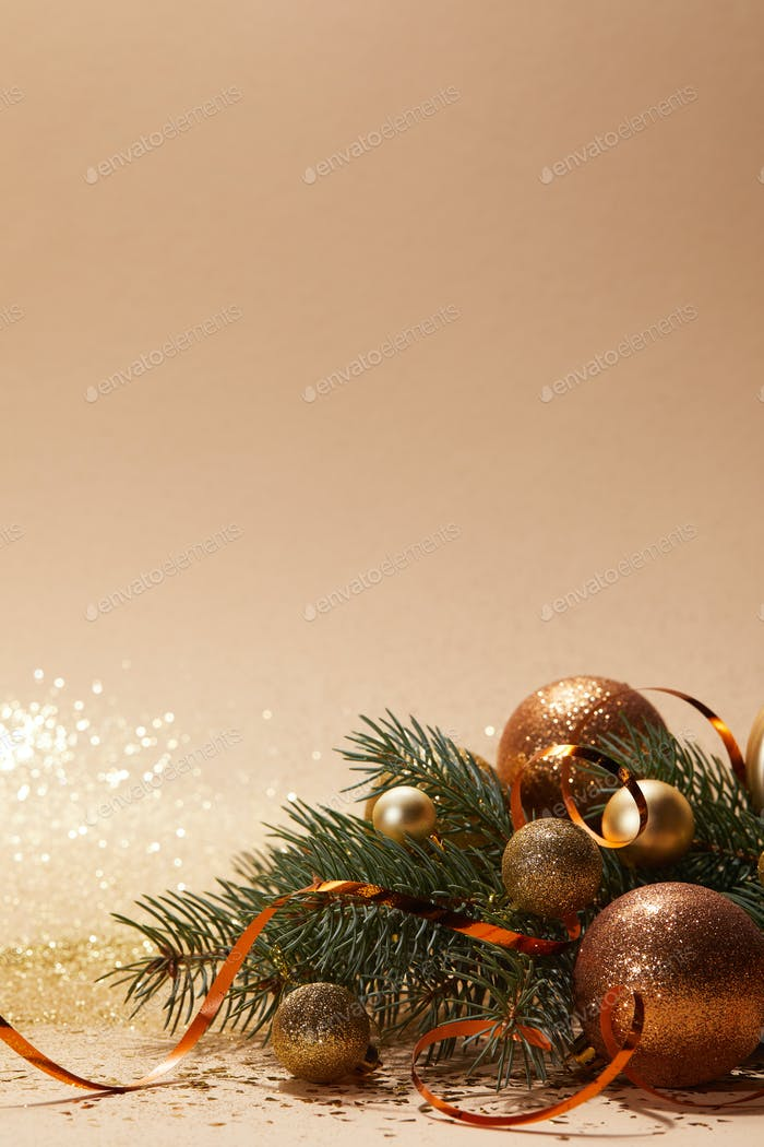 glittering golden christmas balls and christmas tree branch on tabletop