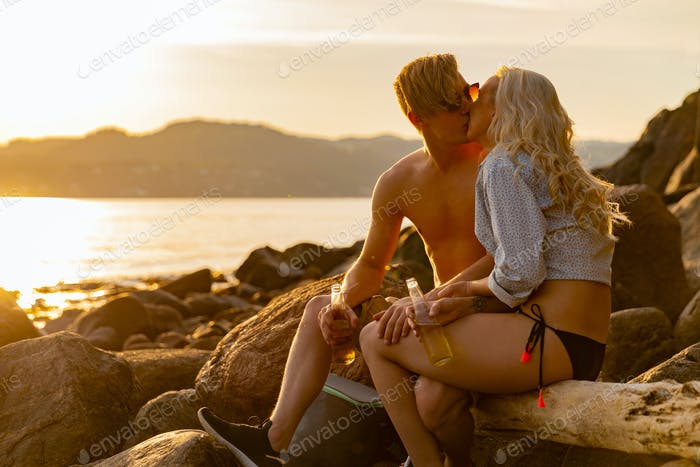 Romantic Couple Kissing And Drinking Beer While Sitting On Rocks