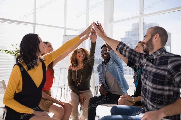 Group of happy executives giving high five to each other