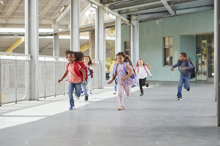 Elementary school kids running in school corridor, side view