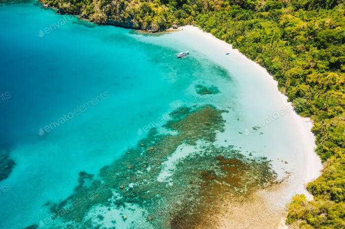 Aerial drone view of lonely boat at beautiful deserted tropical beach and blue lagoon surrounded by