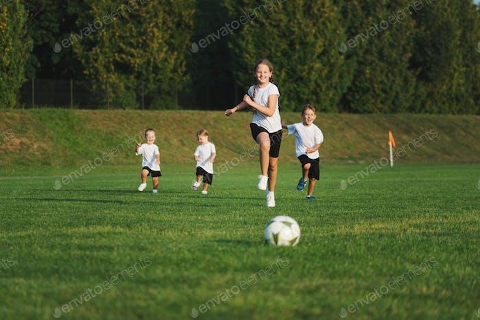 kleine glückliche Kinder auf Fußballplatz