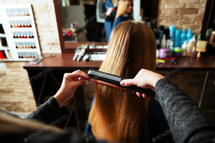 Woman hairdresser using curling iron.
