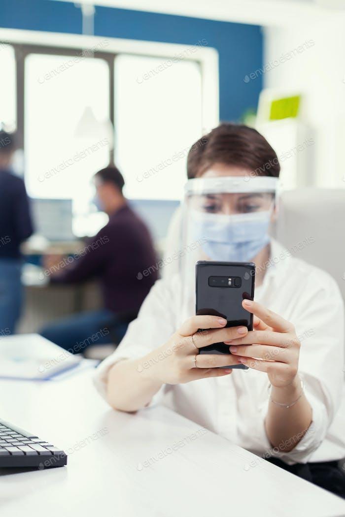 Mujer de negocios utilizando mensajes de texto del teléfono móvil en el teléfono inteligente