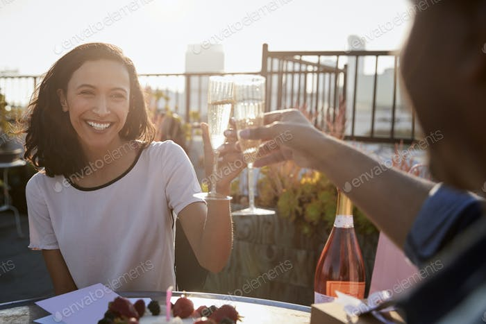 Couple Making Toast To Celebrate Birthday On Rooftop Terrace With City Skyline In Background
