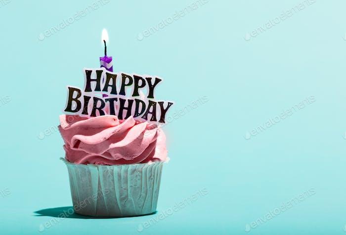 Geburtstagsmuffin mit Kerze auf blauem Hintergrund.
