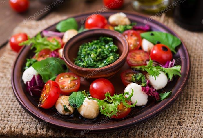 Caprese Salat Tomaten und Mozzarella mit Basilikum und Kräutern auf einem braunen Teller