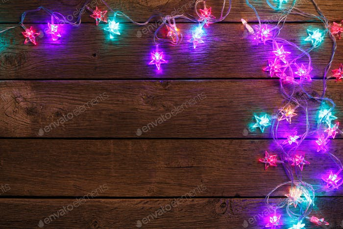 christmas lights border on wood background