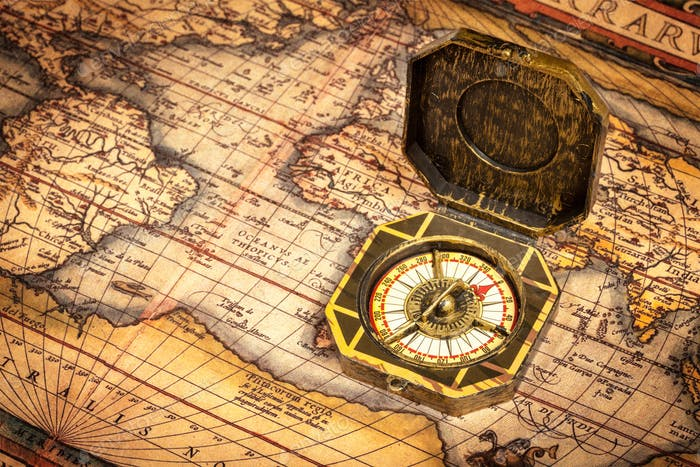 Vintage pirate compass on ancient map