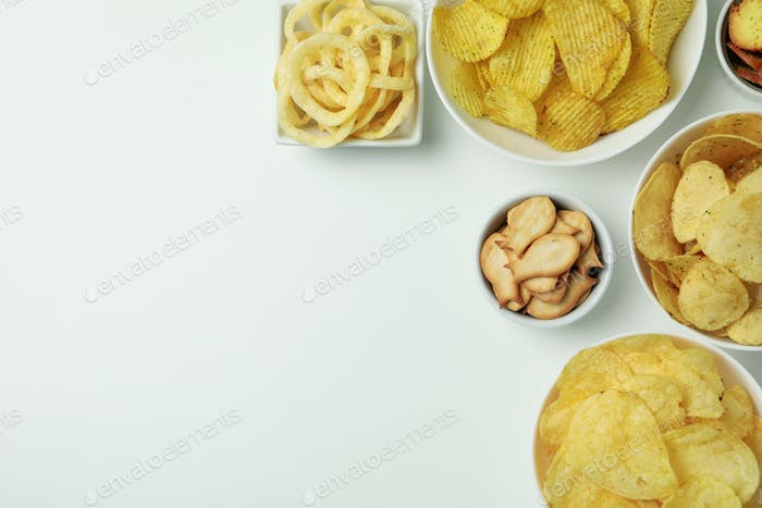 Bowls with different snacks on white background
