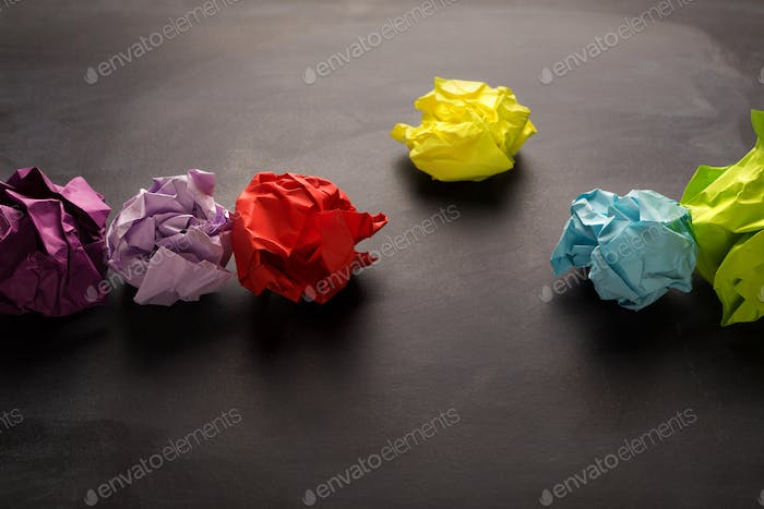 Multicolored crumpled paper balls over black background